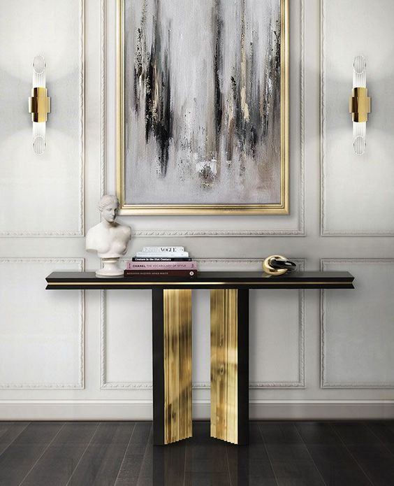 a refined black and gold console plus a matching grey, black and white artwork in a gilded frame