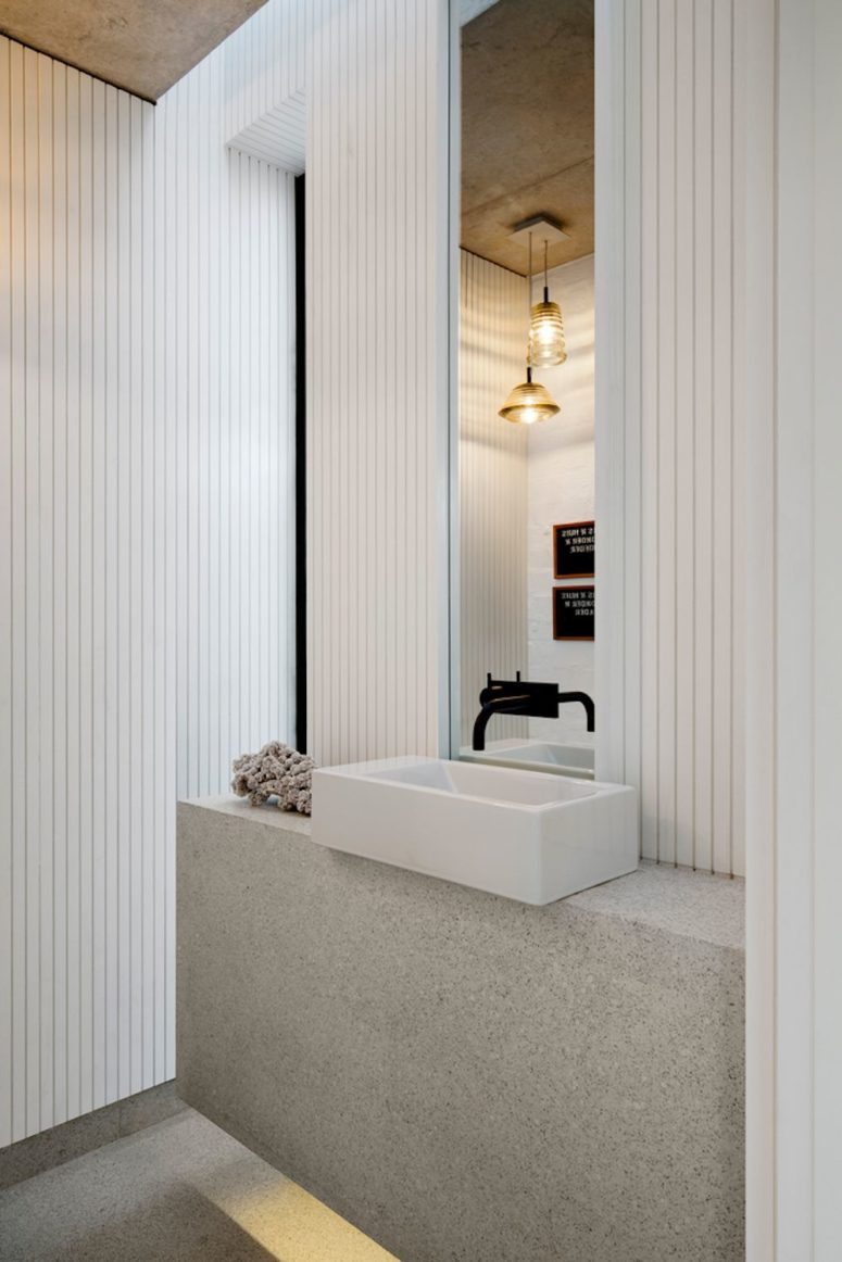 White wooden slabs and a stone sink stand create an elegant and modern feel