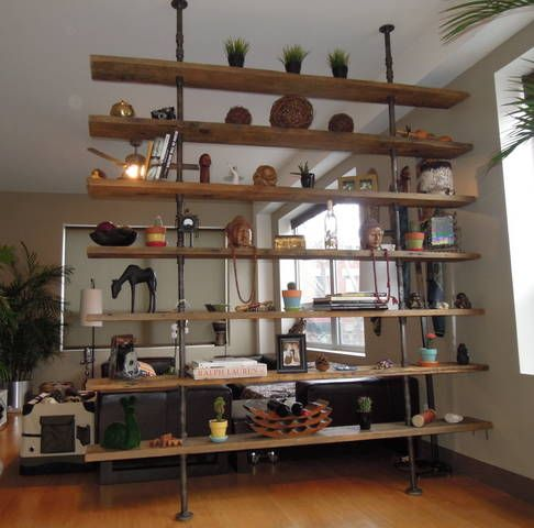 a large industrial shelving unit separates the living room and kitchen and adds an industrial feel to the space