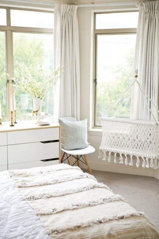 a peaceful light colored space with boho touches and a woven crib hanging by the window looks heavenly