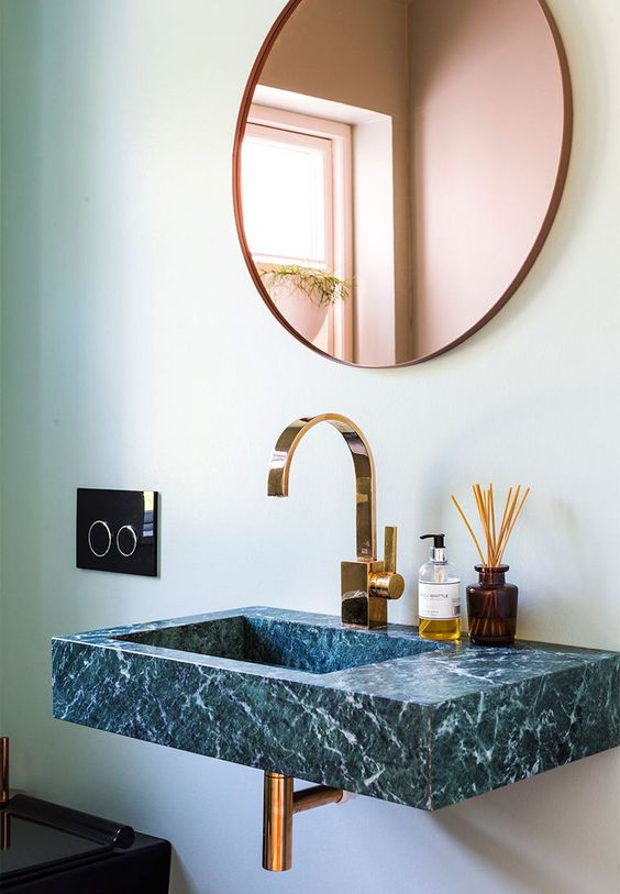 a stunning green marble sink with luminaire and mirror in brass