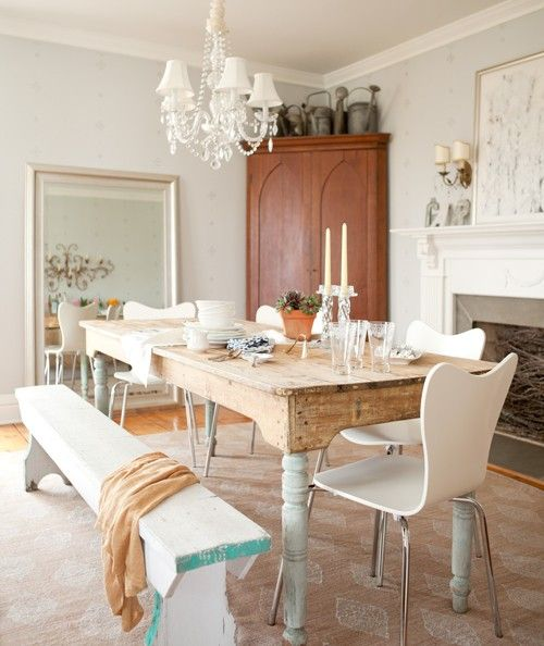 an antique table with whitewashed legs and modern white chairs and a bench for a softer vintage look