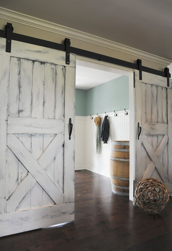 the soft whitewashed shade of the doors contrasts the exposed hardware and create a unique combo