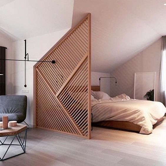 a creative geometric plywood space divider that perfectly fits the space and highlights the attic roof