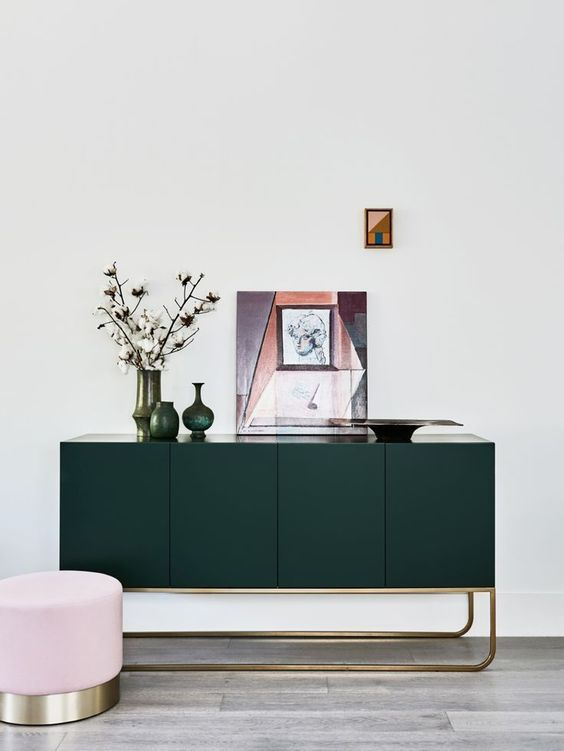 a forest green console with gilded touches is a chic and refined idea