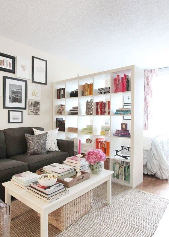 a large white IKEA KALLAX shelving unit is a great space divider that lets light in and allows much storage