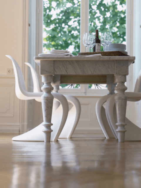 a refined dining table and white sculptural modern chairs of the same shade to make the look not so different