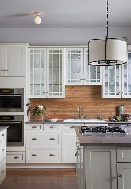 traditional white cabinets are warmed up with a light-colored wood backsplash
