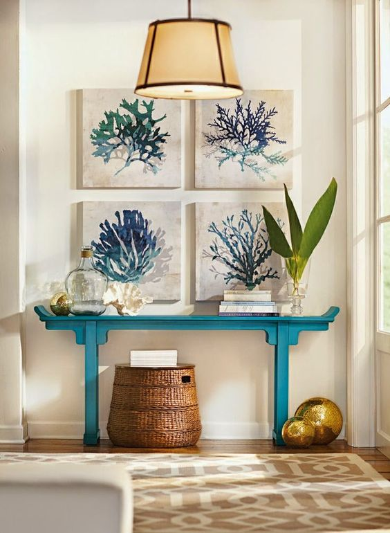 a coastal entryway with a turquoise console table, a basket and a gallery wall of watercolor sea artworks