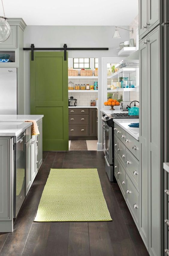 a grass green painted barn door separates the kitchen and pantry and adds a cute colorful touch