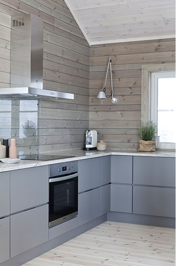 a minimalist chalet kitchen with sleek grey cabinets and wooden plank walls plus a glass screen