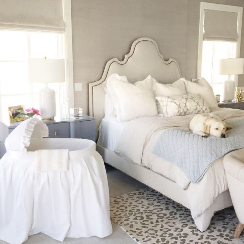a preppy bedroom with a vintage feel and a fabric covered crib by the bed