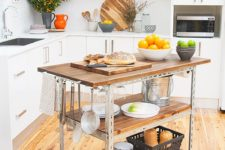 16 a simple industrial kitchen island of steel and reclaimed wood on casters features two open shelves