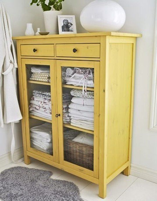 a yellow cabinet with glazing is a great idea to store towels in a rustic bathroom