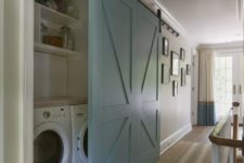 17 a large light blue barn door is used to hide a built-in laundry and keep the space neat