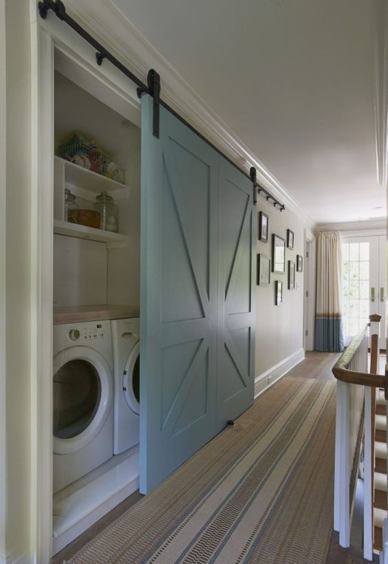 a large light blue barn door is used to hide a built-in laundry and keep the space neat