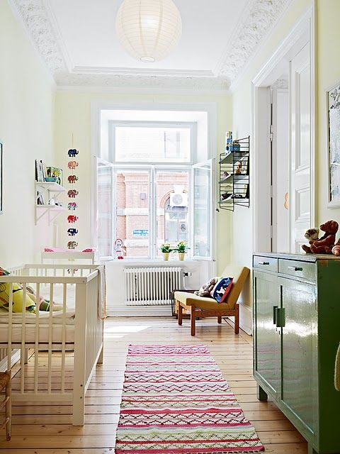 a large window and some simple paper lamps are all the you need for a comfy nursery