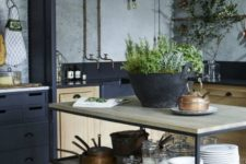 17 a simple industrial kitchen island with black metal framing and light-colored wooden tops and shelves for storage