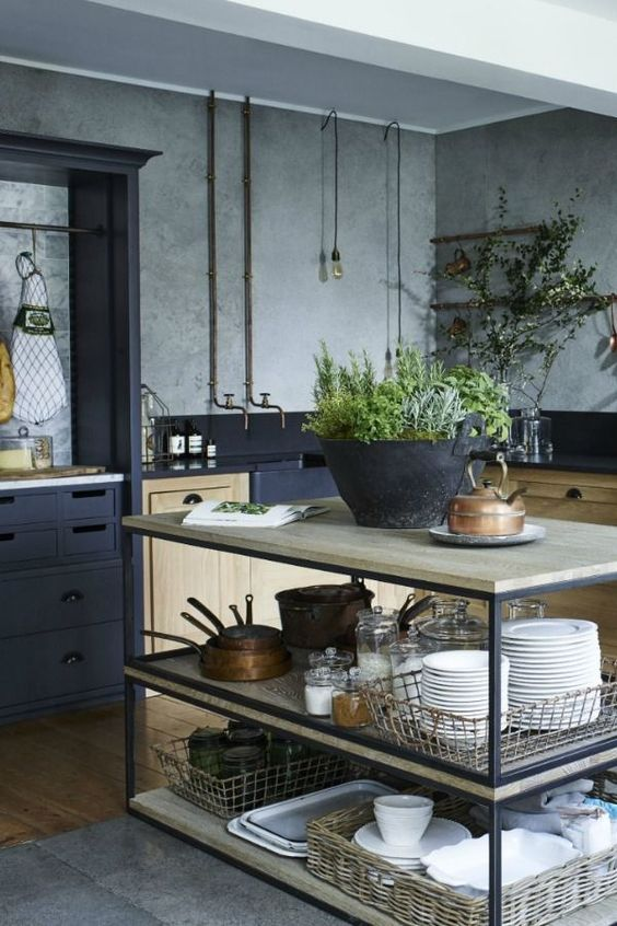 a simple industrial kitchen island with black metal framing and light-colored wooden tops and shelves for storage