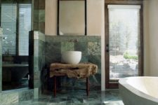 17 a stunning natural bathroom with green marble tiles, a raw wood slab vanity and wooden touches