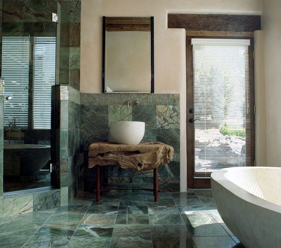 a stunning natural bathroom with green marble tiles, a raw wood slab vanity and wooden touches