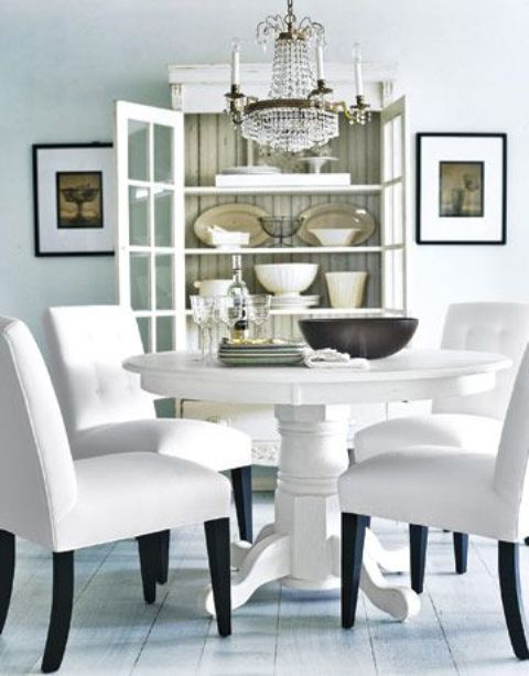 a white vintage round table and modern chairs with white upholstery for a refined and chic space