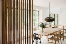 17 a wood plank space divider that separates the dining space from the kitchen and lets light in