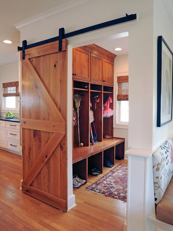 a light-colored sliding barn door can be used to hide a small mudroom or another functional space