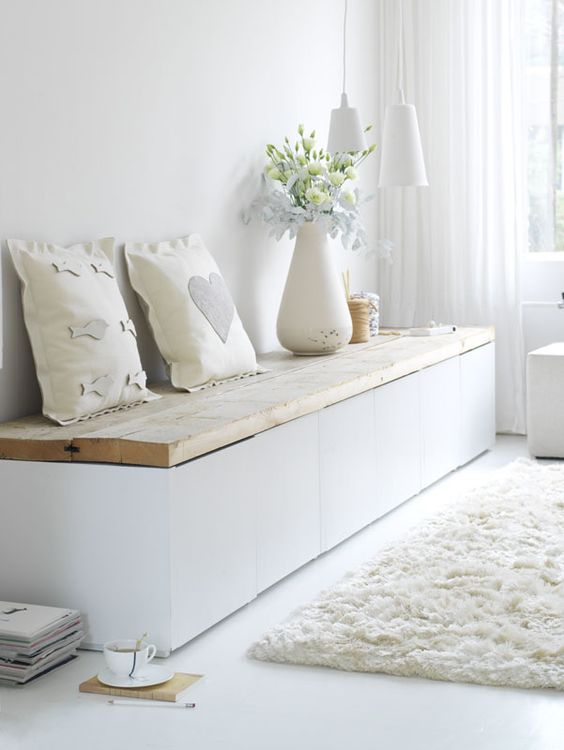 a modern white bench with a wooden plank top and much storage space inside