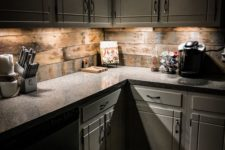 18 a rustic off-white kitchen with a stone countertop and a reclaimed wood backsplash plus additional lights