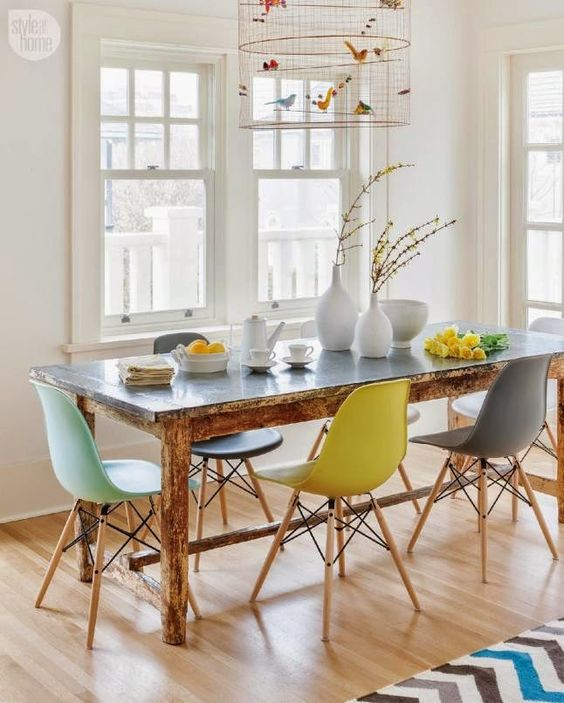 a vintage rustic table plus modern colorful chairs and a faux bird cage with colorful faux birds