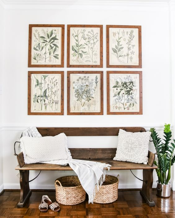 a wooden bench, wicker baskets and a gallery wall with botanical art for a natural feel