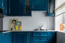 18 bold blue cabinets make a colorful statement here and raise the mood making maximum of a small space