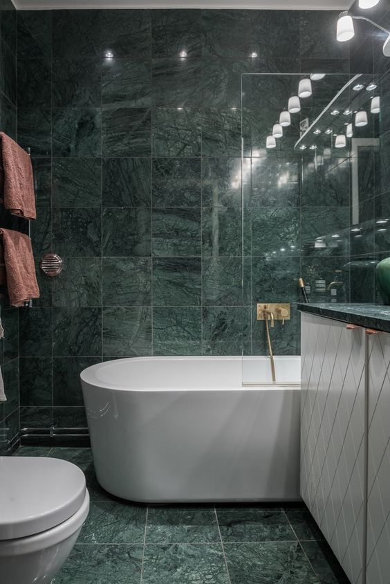 green marble tiles covering the whole bathroom make it a refined and a bit moody space