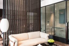 18 wood plank and light fabric space divider separates the living room and the bedroom gently and with style