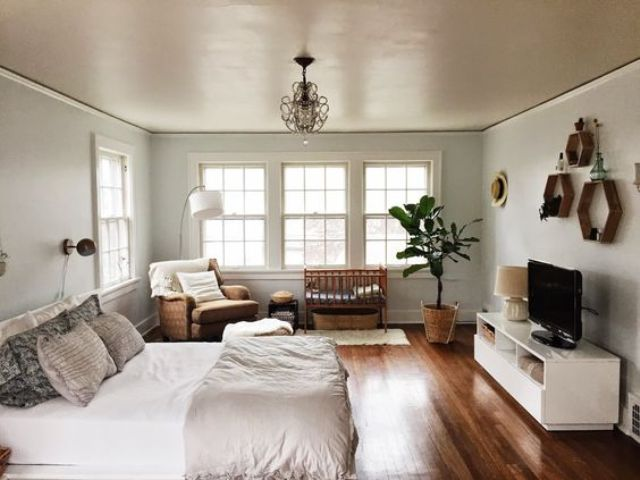a calm and welcoming space that includes a master bedroom and a nursery nook by the window, everything in the same style