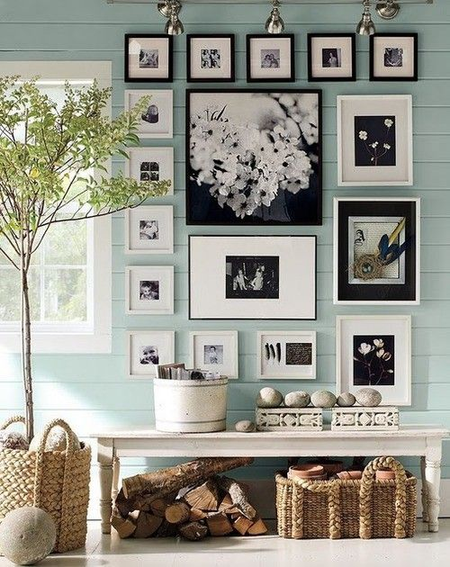 a country house entryway with mint walls, baskets and a gallery wall in black and white for a statement
