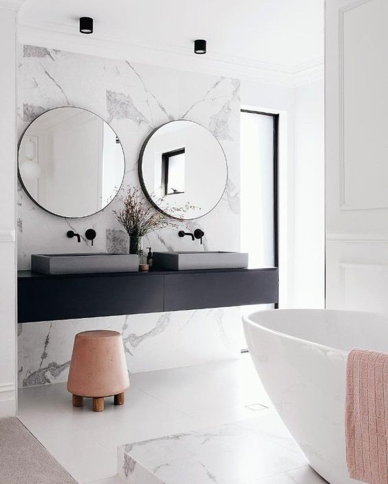 a gorgeous marble accent wall and bathtub platform make the space peaceful and refined