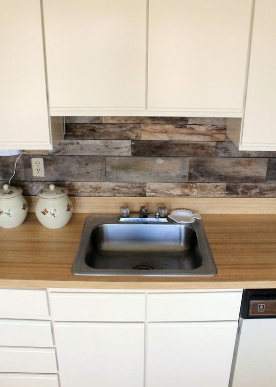 cream sleek cabinets, a light-colored wood countertop and a backsplash of reclaimed wood for a unique look