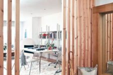 wooden plank screens on both sides divide the home office from the entryway