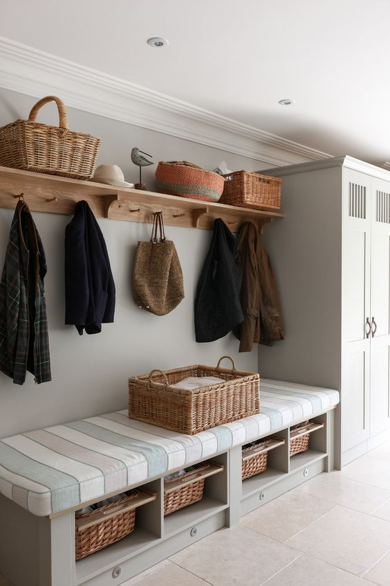 a bench with a striped mattress on top and some woven baskets as drawers inside