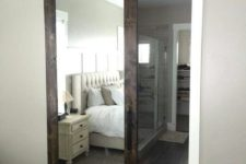 20 a dark stained barn door with a mirror insert hides a bathroom and a closet