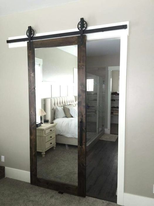 a dark stained barn door with a mirror insert hides a bathroom and a closet