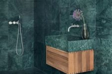 20 a minimalist bathroom fully covered with green marble tiles that are contrasting light-colored wood