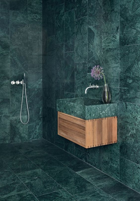 a minimalist bathroom fully covered with green marble tiles that are contrasting light-colored wood