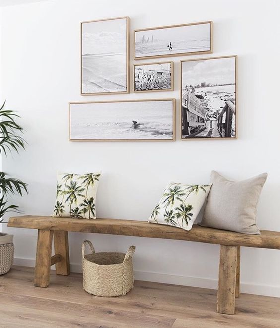 a natural space with a wooden bench and a black and white gallery wall with matching frames