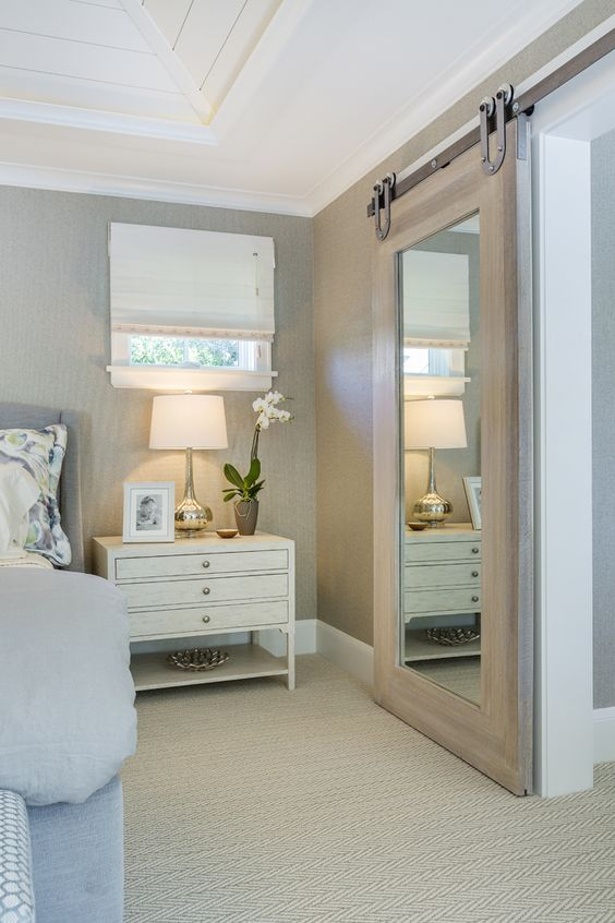 a light-colored barn door with a large mirror can be used for dressing up in the bedroom