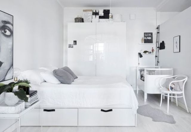 a monochrome Scnadinavian bedroom with minimalist furniture and a crib in the corner, a chair and lights are a must there