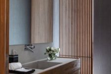 21 a vertical wooden plank screen separates the bathroom into two parts but lets light in