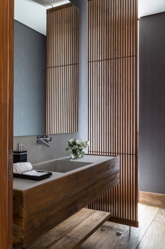 a vertical wooden plank screen separates the bathroom into two parts but lets light in